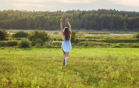 Adult girl running into willdness: sunlight meadow, lake and forest, copy space, connection with nature and summer vacation concept