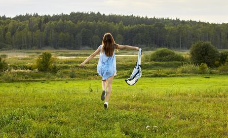 Beautiful woman runnig into the wild nature and waving her sacrf, meadow, lake and forest in the background, copy space, lifestyle, connection with nature concept