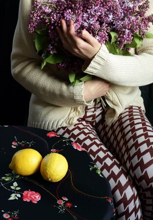 Woman holding a bouquet of blooming lilac with a hand gesture sitting at the table with lemons on it, body part crop, closeup, copy space, vertical Standard-Bild