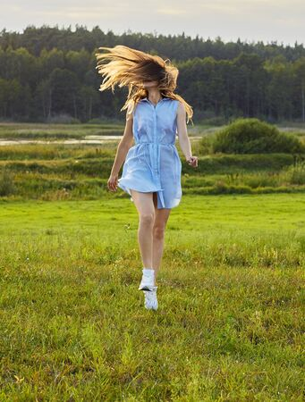 Beautiful adult girl jumping in the wild nature: meadow, lake and forest, female in blue dress happy shake her hair, copy space, lifestyle, connection with nature concept