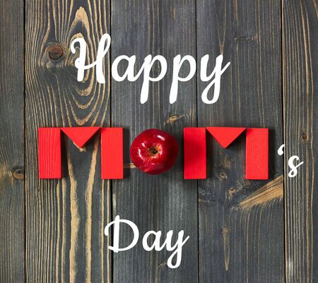 Happy mom's day postcard on the background of Mom word from red toy bricks and an apple flat on dark textured wood, closeup, copy space, from above top view, mother's day and zero waste concept