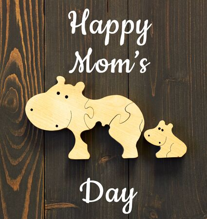Happy mom's day postcard on the background of wooden hippo toy in child's hand flat on wood table, closeup, copy space, from above top view, mother's day and zero waste concept