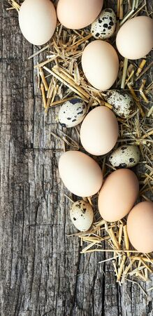 Eggs flat composition on straw on textured wood background, copy space, closeup, vertical, flat lay, from above top view, easter concept and design Standard-Bild