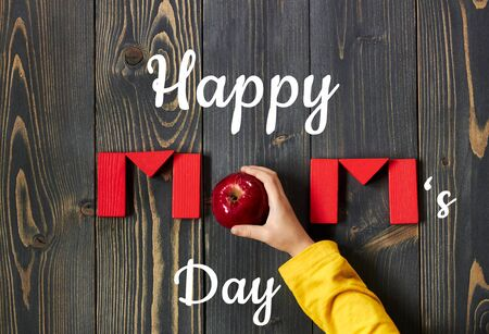 Happy mother's day postcard on the background of Mom word from red toy bricks and an apple with child hand flat on dark textured wood, closeup, copy space, from above top view, mother's day and zero waste concept