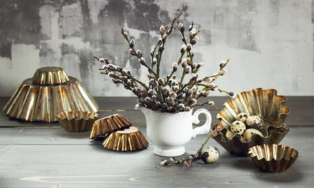 Willow bouquet in a vase on palm sunday with quail eggs and cake mould on wooden table, closeup, easter religious holiday concept