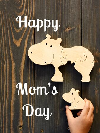 Happy mother's day postcard on the background of wooden hippo toy in child's hand flat on wood table, closeup, copy space, from above top view, mother's day and zero waste concept Standard-Bild