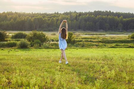 Adult female walking into willdness: sunlight meadow, lake and forest, copy space, connection with nature and summer vacation concept