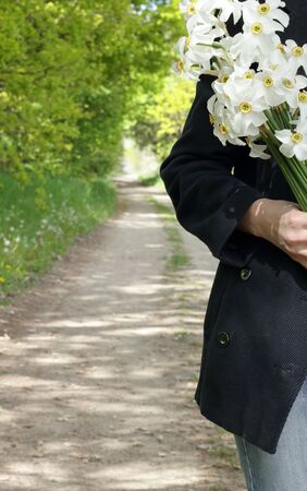 Casual dressed woman walking in the wild nature with a bouquet of daffodils, crop, closeup, copy space, connection to the wilderness lifestyle concept