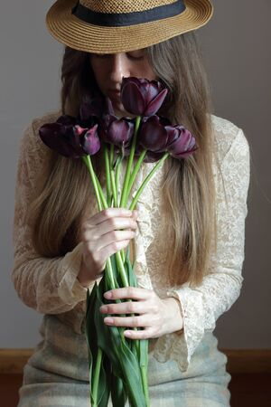 Young bohemian woman in vintage retro cloth and a hat smelling bouquet of purple tulips, creative sensual female portrait, vertical