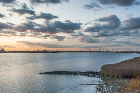 Autumn sunset at the Schelde river with a view of the Antwerp harbor industries