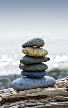 Balanced stones on driftwood along the beach