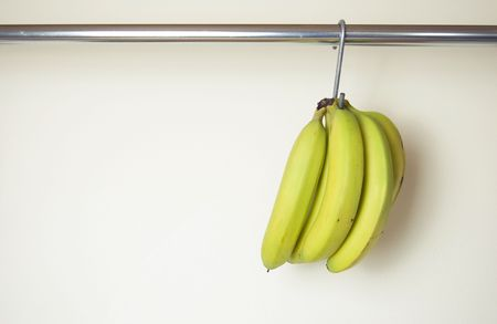 Ripened bananas hanging from a hook in the kitchen