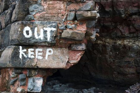 Entrance to dark cave with warning painted on rocks Stock Photo