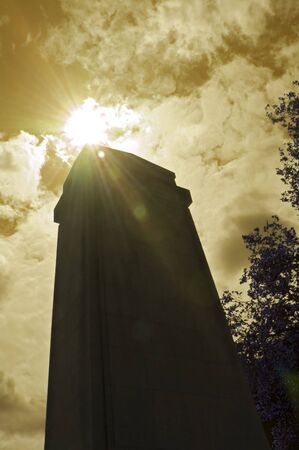 Silhouette of World War 1 and 2 oblelisk against bright sun