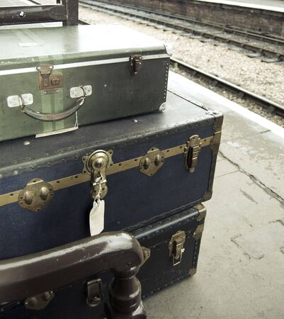 Old-fashioned personal baggage stacked up on train platform