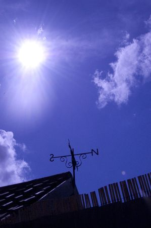 Silhouette of weather vane against blue sky Stock Photo