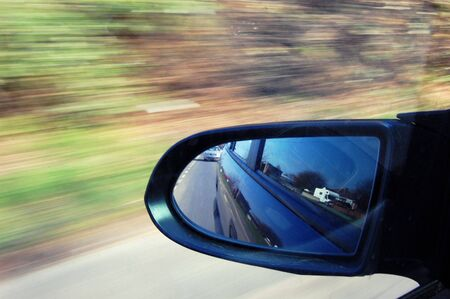 Wing mirror of car at high speed, view of traffic behind