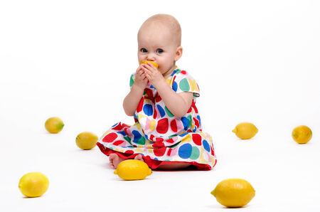 cute baby girl: Cute baby girl sitting on the floor playing with lemons