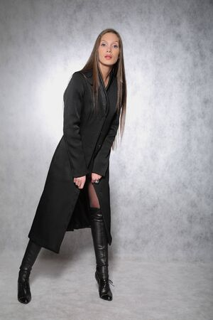 Young woman in a coat posing photo