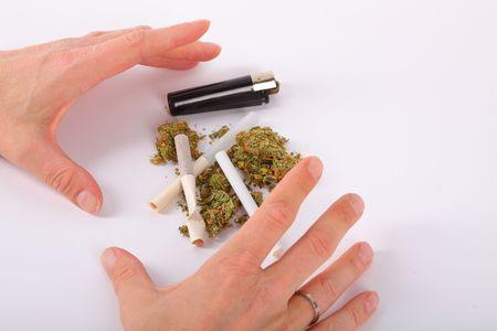 Hands grabbing marijuana, cigarettes and lighter photo