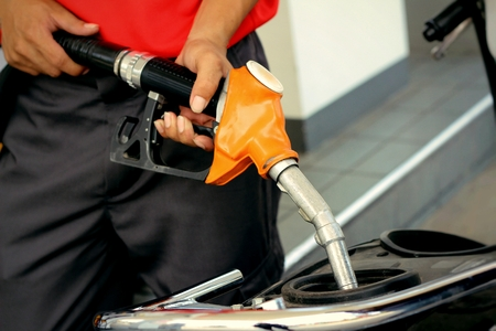 fueling: hand fueling fuel with motorcycle Stock Photo
