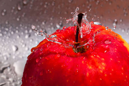 splash water on the red apple photo