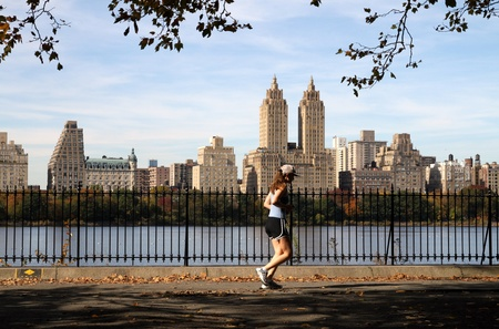 New York, NY, USA, October 2009 - Central Park reservoir with jogger and luxury apartment buildings in background