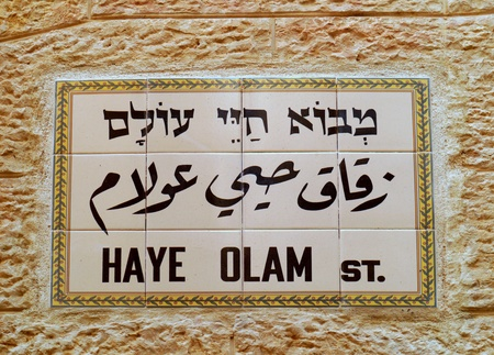 Jerusalem, Israel, October 2011 - street sign in the Old City, it consists of ceramic tiles embedded in the stone wall of a building, trilingual in Hebrew, Arabic, and English characters.  The name of this street means 'Eternal Life'