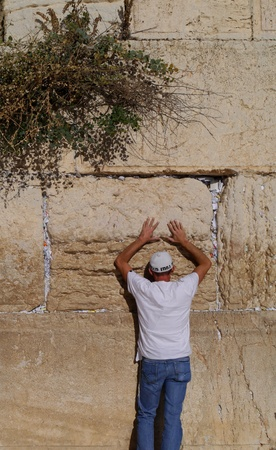 Jerusalem, Israel - October 2011:   A Jewish man prays at the Western Wall, the holiest site of Judaism.   The cracks between the stones are full of the traditional notes to God.