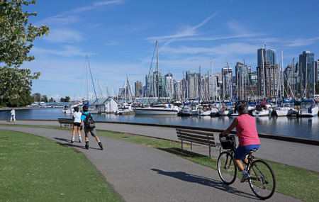 seawall: VANCOUVER - JULY 2015: Stanley Park is Vancouvers most visited attraction, and the seawall path for cyclists and joggers gives great views of the harbor Editorial