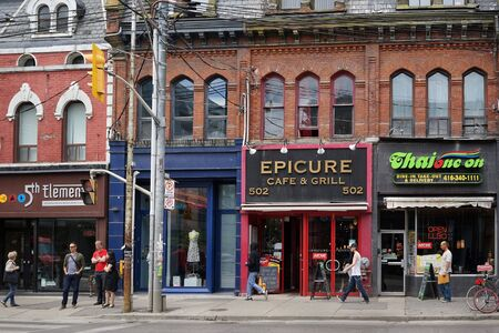 TORONTO - 2015:  Victorian architecture is preserved on Queen Street West, and used for diverse ethnic restaurants Editorial