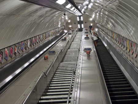 high angles: LONDON, ENGLAND - 2013:  The escalator leading to the trains at some underground stations such as this one at Westminster is very steep in order to go under the river, as seen in London circa 2013.