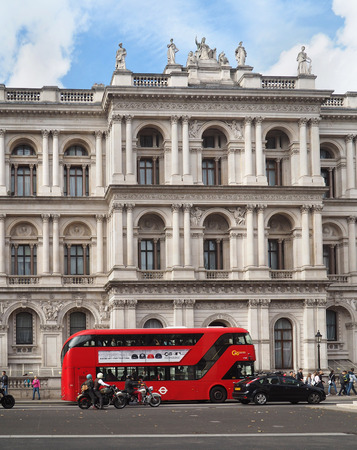 statutes: LONDON - SEPTEMBER 2016:  An iconic red double decker bus passes in front of a baroque government building in  Whitehall, as seen in London circa 2016.