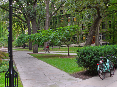 shady: shady college campus with ivy covered building and student cyclist