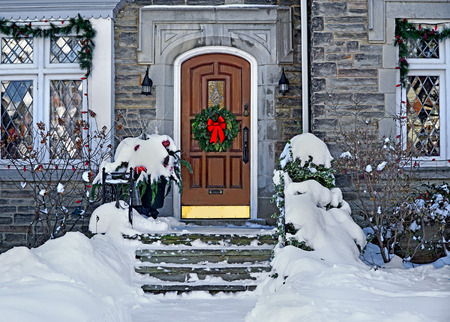 Weiße Haustür mit Weihnachtskranz an einem verschneiten Tag Standard-Bild - 68081991