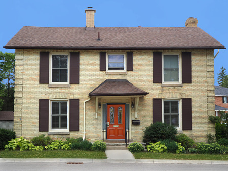 two story yellow brick house with shutters Editorial