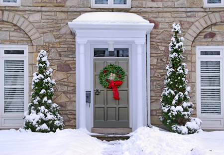 front door with colorful wreath in winter scene