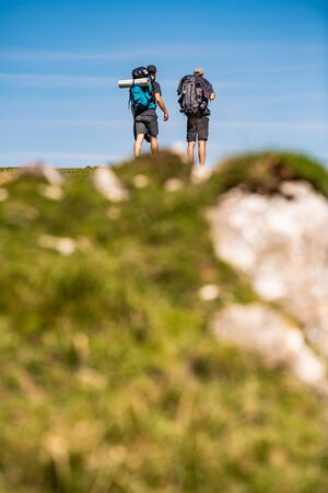 Pilgrims with backpack walking the Camino de Santiago in Pays Basque, France