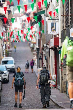 Pilgrims with backpack walking the Camino de Santiago, Saint Jean Pied de Port in Pays Basque, France