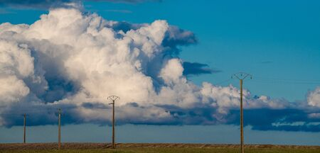 France, Charente, Electric line crossing the landscape with a cloudy sky