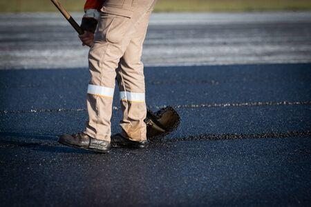 Worker with roller compacting asphalt on a road 版權商用圖片