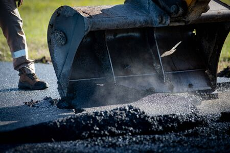 Laying fresh asphalt on construction site on a road