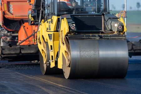 A roller compacting asphalt on a road Foto de archivo