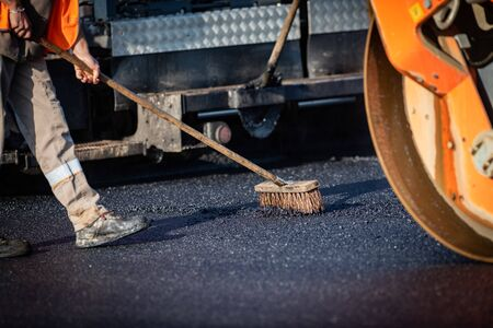 Worker with roller compacting asphalt on a road Foto de archivo