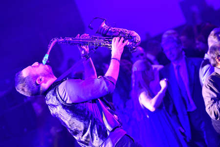 Musician with saxophone in purple light Editoriali