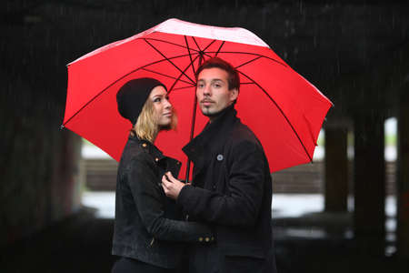 benevolence: love young people under the red umbrella Stock Photo