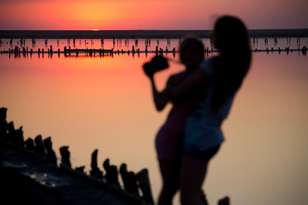 on a salt lake two girls are blurred against the background of the horizon, photographed at sunset and in summer Zdjęcie Seryjne
