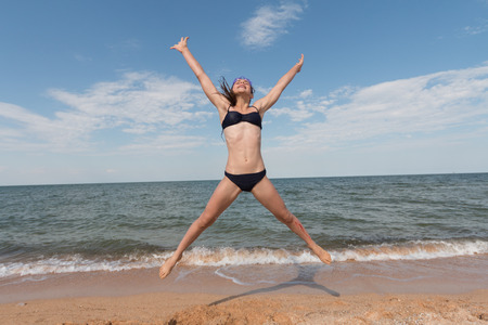 Young girl athlete in a swimsuit on the sea jumping on the beach on the sand, legs and arms are open Stock Photo