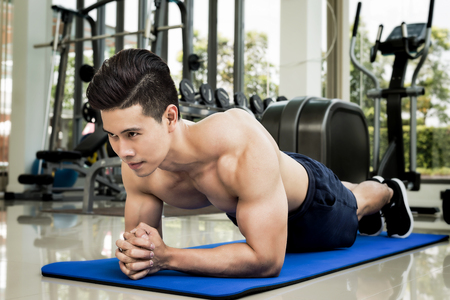 Handsome Young Athletic Man Doing Plank and Workouts in the Gym - Sport and Healthcare Concept Stock Photo