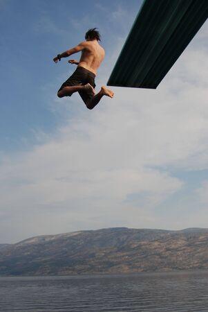 Man jumping from a jumping board into okanagan lake. Stock Photo - 3850177